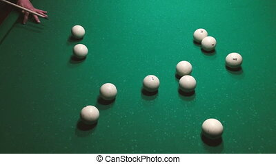 Man supports cue by hand and aiming billiard ball closeup.