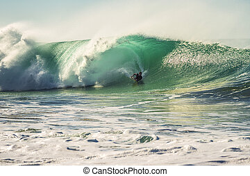 man surfing a powerful and big wave at sunset