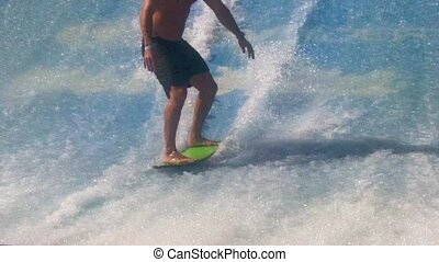 Man surfing on a surfboard over Flowrider
