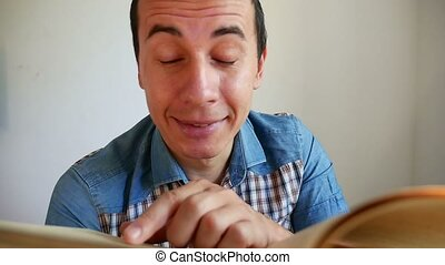man surprised joyful thinks reading turns the page video a book sitting in the room