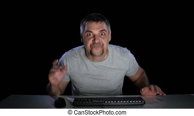 Man surprised, looking sad, news on the internet, emotions of surprised, front of a computer monitor, gray t-shirt, watching online, sits by the table, mouse, keyboard, unshaven, studio