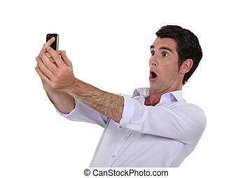Man surprised watching his mobile phone