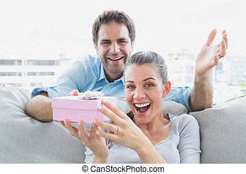 Man surprising his delighted girlfriend with a pink gift on the sofa at home in the living room