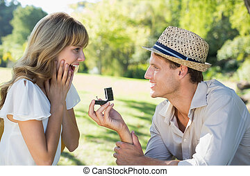 Man surprising his girlfriend with a proposal in the park on a sunny day