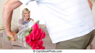 Man surprising his partner with a bouquet of roses on the...
