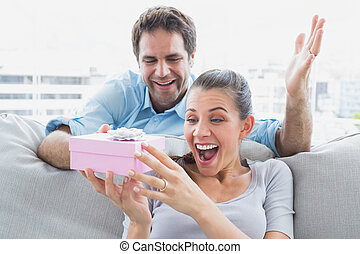 Man surprising his pretty girlfriend with a pink gift on the sofa at home in the living room