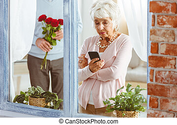 Man surprising woman looking at telephone