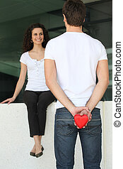 Man surprising woman with heart-shaped gift