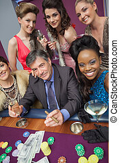 Man surrounded by beautiful women at roulette table