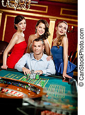 Man surrounded by young girls gambles roulette