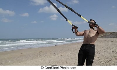 Man suspension training with fitness straps on the beach
