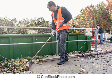 Man sweeping the floor of recycling center after delivering...