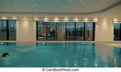 Man swimming alone in the indoor pool