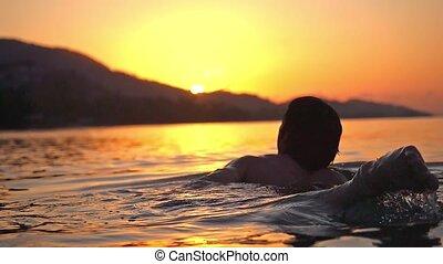 Man Swimming at Sunset Background and splashing sea in slow motion.