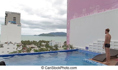 Man swimming in a roof top luxury swimming pool.