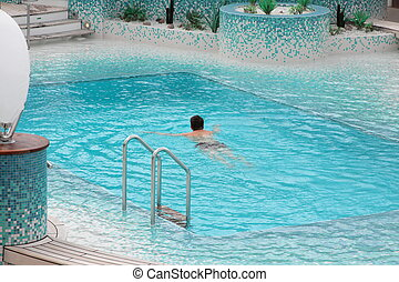 Man swimming in blue water of the pool