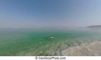 Man swimming in pure salt water of Dead Sea, Israel - Man...