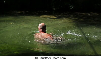Footage clip in slow motion of a moscular and atractive man swimming in the lake illuminated with sunrays.