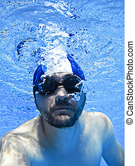Man swimming with glasses underwater in pool