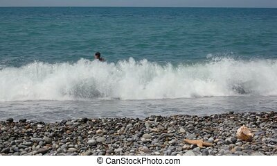 man swims in sea, then got out of the water and comes to camera
