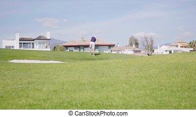 Man swinging golf club on golf course - Man in dark shirt...
