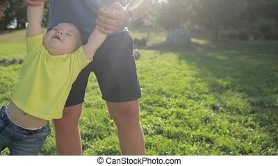 Man swinging his toddler baby boy by hands in park