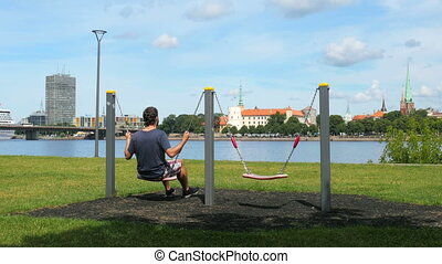 """man swinging on swing, watching riga view, latvia"""