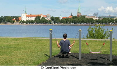 """man swinging on swing, watching riga view, latvia"""