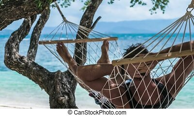 Man swinging relaxed in a hammock on the beach in front of the blue ocean. Hiding him from the sun in the shadow of a wizard trees. Haad Rin, Koh Phangang.