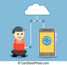 man synchronizing smartphone with notebook