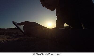 Man tablet. man holding a tablet, on the Internet a web page flips through the silhouette of sunset