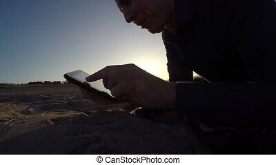 Man tablet. man holding a tablet, on the Internet web page flips through the silhouette of sunset
