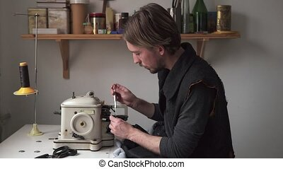 Man tailor sew fur on furrier machine in workshop - Young...