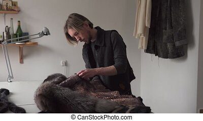 Man tailor touching fur for sewing coat in furrier workshop...