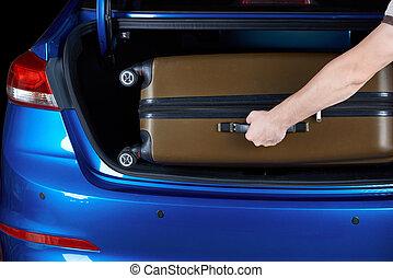 Man take luggage bag from car trunk