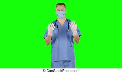Man take off and puts on his surgical gloves. Green screen