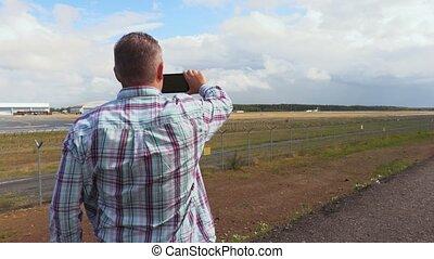 Man take photos on smartphone near airport runway