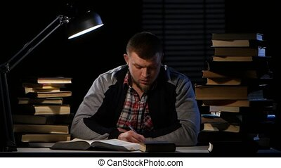 Man takes a book and writes the information itself. Black background