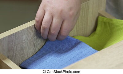 Man takes a cotton kitchen towel from the shelf. Close up of...
