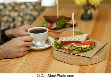 man takes a cup of coffee from a wooden table, on which lies a sandwich