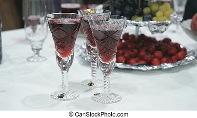 Man takes a glass of red champagne from the table