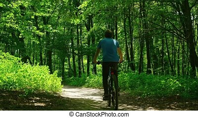 Man takes a walk in the woods on a bicycle