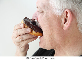 man takes bite of doughnut