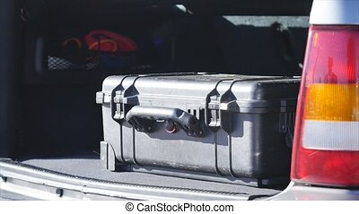 man takes case or bag from the car trunk.
