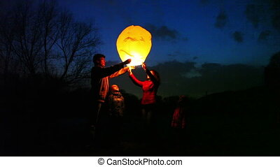 man takes glowing chinese lantern from wife, does attempts to start it, she with son and daughter look, part1