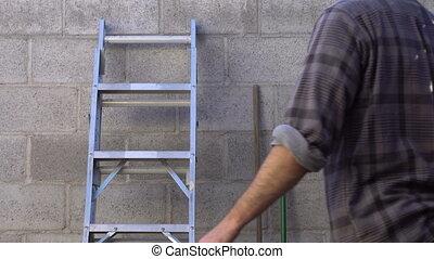Man Takes Ladder Away Outdoors - Outdoor shot of a man...