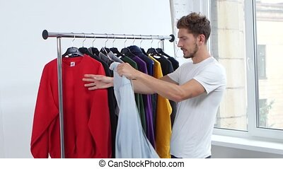 Man takes off his clothes from a hanger, thinks what to put on him