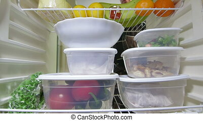 Man takes out stack of food plastic containers from fridge, view from inside