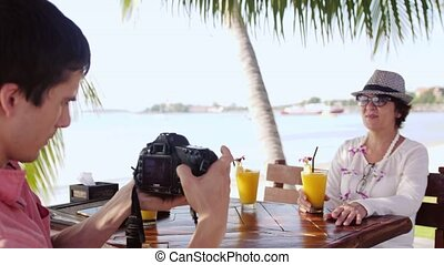 Man takes photo his mum with camera in outdoor cafe on resort by tropical beach.