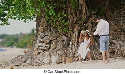 Man takes photo of beautiful woman in hat and white dress on a camera Outdoors Under the Tree with roots. Happy smiling man and woman on beach. slow motion, 3840x2160
